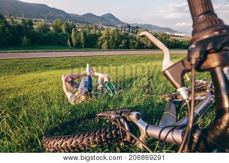 Father with son rest on green meadow after bicykle walk