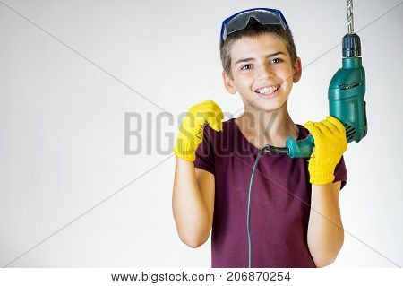 Portrait of young boy holding electric drill. Dreams of future profession. Smiling worker. Cheerful boy using electric drill. Happy boy holding drilling machine.