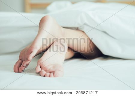 The feet or foot of couples sleeping on the bed and cover by the white blanket on a bright Sunday morning.