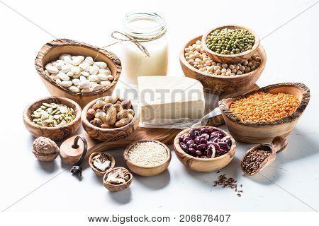 Vegan protein source. Tofu, vegan milk, beans, lentils, nuts and seeds on white table. Healthy vegetarian food.