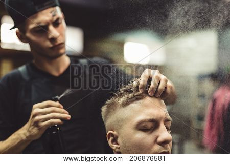 Professional hairstylist applying spray on hair of customer after styling. poster