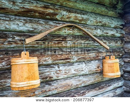 Ancient yoke with buckets. Hanging on the wall of a wooden house.
