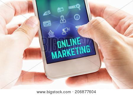 Close Up Two Hand Holding Mobile Phone With Online Marketing Word And Icons On Blurred Blue Backgrou