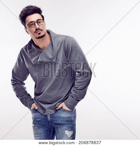 Handsome young Fashion guy. Autumn Trendy Outfit, Glasses. Sporty Confident Brunette Bearded man with hands in pockets. Stylish Hairstyle, fashionable gray jumper. Studio fashion pose, white background
