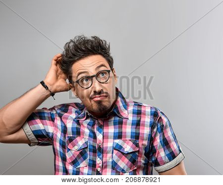 Handsome young man Thinks Idea, Crazy. Portrait Hipster Nerd Loser guy in Trendy shirt, Glasses. Brunette Bearded Emotional man, Stylish fashion Hairstyle on gray background. Blue Eyes