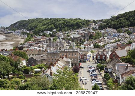 Mumbles, UK: June 23, 2016: View of Oystermouth a coastal fishing village in bygone days. A popular location for tourists all year round. People walking, a residential district and parked cars.