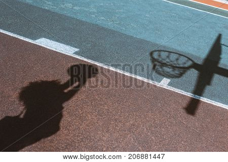 Shadow Of Woman Throwing Ball