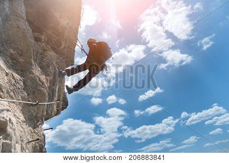 Silhouette of via ferrata climber climbing on rock