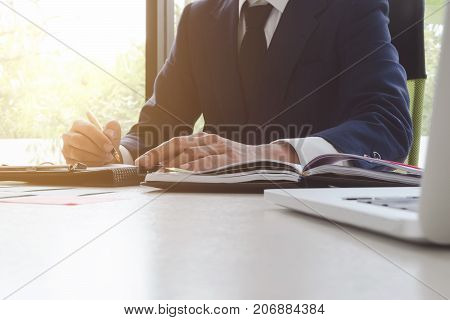 Close-up Of Businessman Signing Contract, Writing Paper At The Desk With Pen And Reading Books At Ta