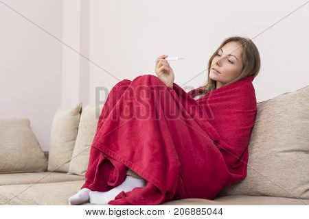 Young woman sitting on a couch covered with blanket having a fever holding a thermometer after measuring temperature.