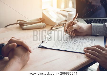 Doctor Hand Holding Pen Writing Patient History List On Note Pad And Talking To The Patient About Me