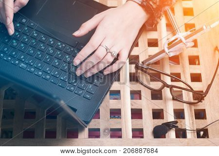 Female blogger writes the text on the laptop. The set of objects for video blogging, lavalier microphone, smartphone, selfie stick, top view