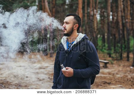 Man With Beard Smoking Electronic Sigarette Outdoor