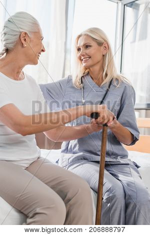Nurse And Senior Woman With Cane