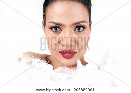 Close up beautiful middle age Asian woman's face with white feathers isolated on white background beauty concept