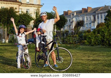 Cheerful family biking in park. Father and two girs ride in the city park. Weekend trip. Active life concept