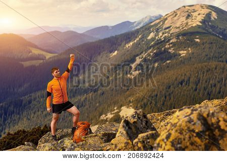 Happy hiker winning reaching life goal, success, freedom and happiness, achievement in mountains. Traveler with backpack stands on the top of mountain