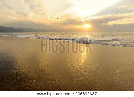 Ocean sunset is a serene scenic seascape on the beach with the bright sun setting on the ocean horizon.