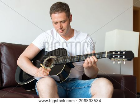 Handsome man compose a song on the guitar.