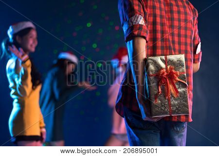 Young handsome man asian hidden gift box for giving girlfriend in christmas party celebrating new year midnight at club