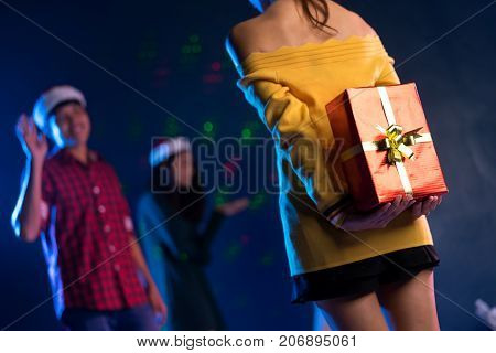 Young beautiful woman asian hidden gift box for giving boyfriend in christmas party celebrating new year midnight at club Closeup girl