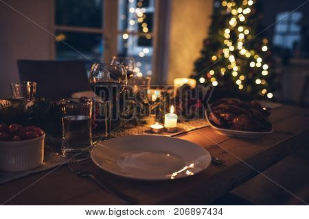 Christmas table decorated with candles and christmas decorative objects. Festive christmas table place setting at home with christmas tree in background.