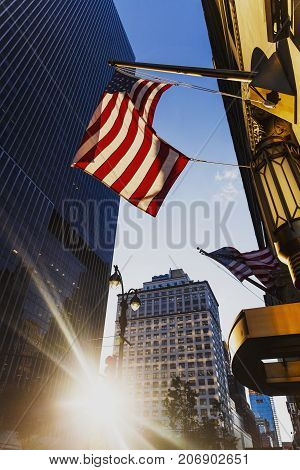 NEW YORK NY - September 7th 2017: Sunflare among buildings in Midtown Manhattan and American flags waving from the entrance of an hotel