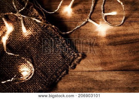 Christmas glowing lights garland on a old antique wooden parquet floor sparkling garland. Christmas background with festive decoration