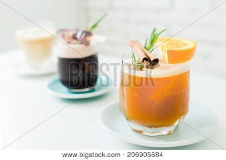 Selective focus of cocktails or mocktails with fruits in glasses.Traditional summer drink alcoholic cocktail with orange and grape in vintage restaurant