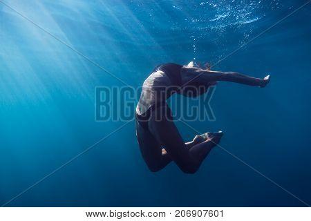 Slim woman swimming in underwater. Sun rays in underwater