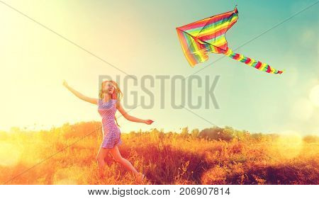 Beauty autumn girl running with kite on the field. Beautiful young woman with flying colorful kite over clear blue sky. Fall. Free, freedom concept. Emotions, healthy lifestyle