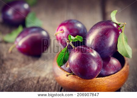 Plum. Healthy juicy ripe organic plums fruit close-up, on wooden table. Prune. Sweet fruit dessert