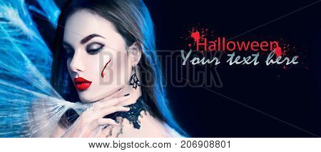 Beautiful Halloween Vampire Woman portrait. Beauty Angry Sexy Vampire Witch lady with blood on mouth posing in darkness, wearing spider web. Art design. Mysterious Model girl with Halloween make up