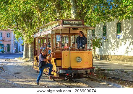 Sintra, Portugal - August 9, 2017: man go up on Tram 7 route Sintra to Praia das Macas. The Sintra tramway, in Portuguese, Eletrico de Sintra, is a popular historic runway with summer races.