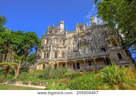 Gothic facade of grand house and gardens of mysterious Regaleira Palace or Monteiro Palace, landmark and Unesco Heritage in Sintra historic center, Portugal. Sunny day, blue sky.