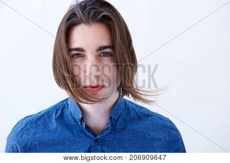 Close Up Handsome Young Man With Serious Expression And Hair Blowing