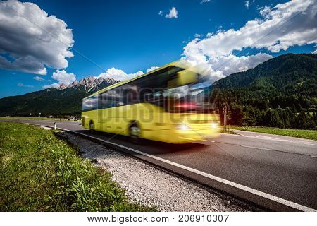 Yellow Public bus traveling on the road in the background the Dolomites Alps Italy. Public transport service. Warning - authentic shooting there is a motion blur.