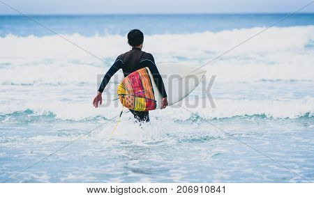 Surfer Guy With Surfboard In Hand Running Towards Big Waves.