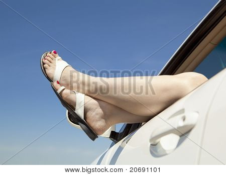 Summer road trip car vacation concept. Woman legs out the windows in car above the clouds. Conceptual freedom, travel and holidays image with copy space.