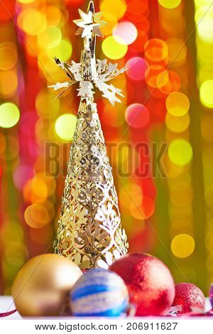 Decorative Christmas tree and Christmas balls on the blured colored light background