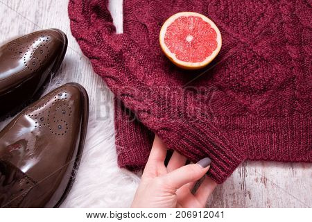 Femaile Hand Holding Maroon Knitted Sweater, Brown Patent Leather Shoes, Cut Grapefruit Halves. Wood