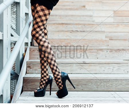 Incredibly long legged girl in fashionable pantyhose and black high heeled shoes posing in the summer on wooden steps. Fashion. Outdoor. Part of body.
