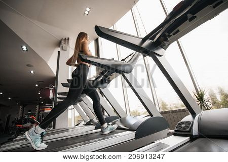 Young slim woman running on treadmill. Beautiful young woman in gym. Running in sport club. shapely pair of legs