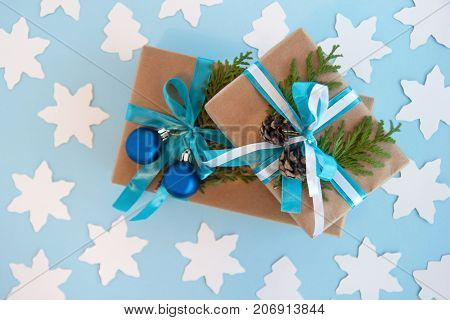 Two Gift Boxes Wrapped Of Craft Paper, Blue And White Ribbon And Decorated Fir Branches, Blue Christ