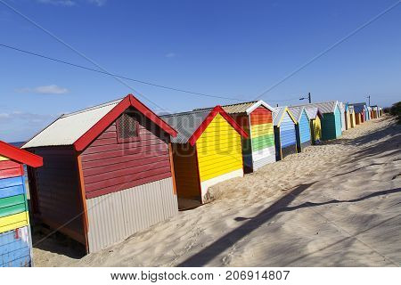 Colorful iconic beach huts on Melbourne's Brighton Beach with summer blue skies and sandy beaches in a diagonal giving diminshing perspective.