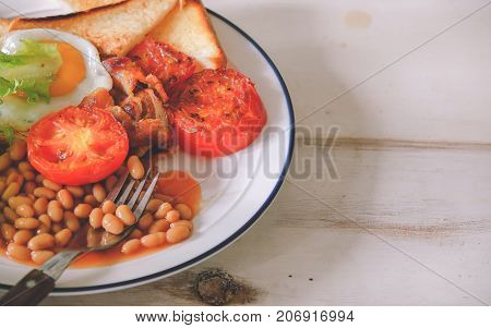 Traditional full English breakfast includes bacon (traditionally back bacon), fried, poached or scrambled eggs, fried or grilled tomatoes, fried mushrooms, fried bread or toast with butter, and sausages