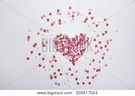 Sugar Sprinkles Candies in Heart Shape Scattered on White Background. Valentine Romance Birthday Charity Symbol. Greeting Card Poster Template.