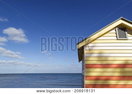 One beach hut on Melbourne's Brighton Beach with a blue sky and ocean background. The brightly painted huts are