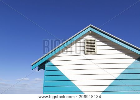 Close up of one of the colorful beach huts on Melbourne's Brighton Beach with a vibrant summer blue sky background