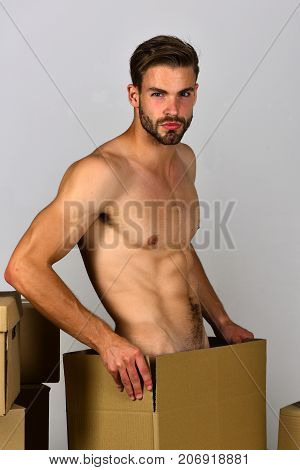 Man Standing Naked Among Cardboard Boxes On White Background